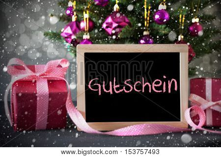 Chalkboard With German Text Gutschein Means Voucher. Christmas Tree With Rose Quartz Balls, Snowflakes And Bokeh Effect. Gifts Or Presents In The Front Of Cement Background.