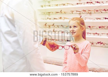 health care, people, eyesight and vision concept - optician giving glasses to little girl at optics store