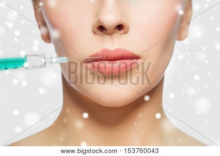 people, cosmetology, plastic surgery and beauty concept - close up of beautiful young woman face and syringe making injection for lips augmentation over gray background and snow