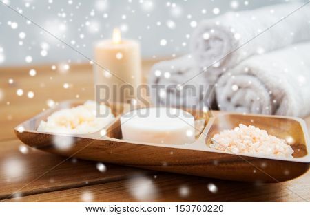 beauty, spa, bodycare, natural cosmetics and bath concept - soap with himalayan salt and body scrub in wooden bowl on table over snow
