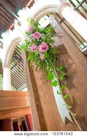 bouquet of wedding flowers on the end of a church pew
