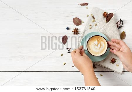 Woman take autumn cappuccino, top view composition. Coffee cup in female hands, latte with foam, cloves, autumn leaves at white wood background with copy space. Fall hot drinks, cafe and bar concept