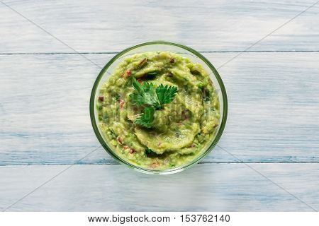 Bowl of guacamole on the wooden table