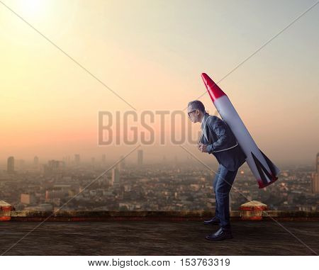 business man carries rocket missile on high building roof against skyscraper scene for business conceptual