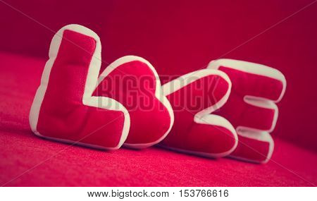Valentines Day background with Soft pillows make word LOVE on red background Vintage Style.