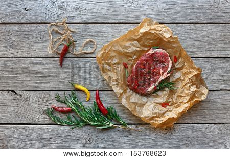 Raw beef steak in craft paper on dark wooden table background, top view. Fresh juicy meat, rosemary and chili peppers. Cooking ingredients, butcher's and grocery concept poster
