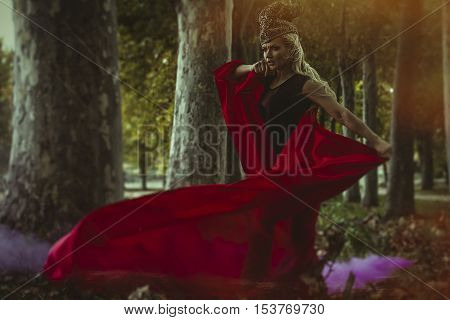 Season, concept autumn blond woman with huge metal helmet and red cape, goddess of forests, fantasy