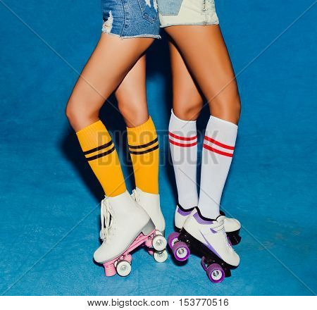 Two long-legged girls in knee socks, half-hose on roller skating vintage derby posing in the skatepark. Part of body.