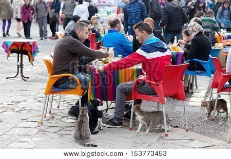 CHEFCHAOUEN, MOROCCO - JANUARY 1, 2014: Men feeding cats on the street.