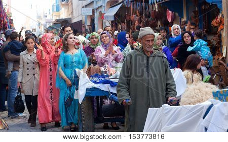 ESSAOUIRA, MOROCCO - JANUARY 15, 2014: Participants of traditional Muslim wedding ceremony walking on the street.