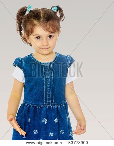 Cute little girl with short pigtails on the head, in a blue dress with short sleeves. Close-up.On a gray background.