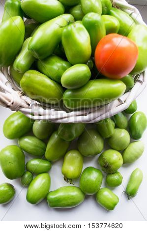 Young green tomatoes in a basket  close up