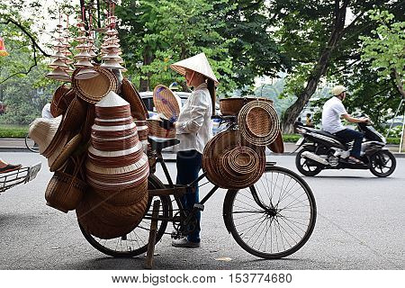 HANOI, VIETNAM, SEPTEMBER 15, 2016 - Unidentified vietnamese girl selling and wearing traditional hat on the streets of Hanoi old quarter