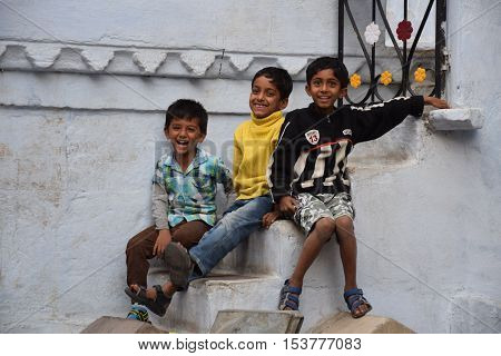 UDAIPUR, RAJASTHAN, INDIA - FEBRUARY 07, 2016 - Three unidentified happy indian kids smiling at the camera while sitting outside the entrance of a house