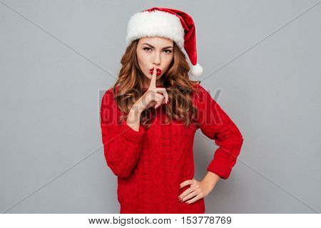 Attractive young woman in santa hat showing silence sign over gray background