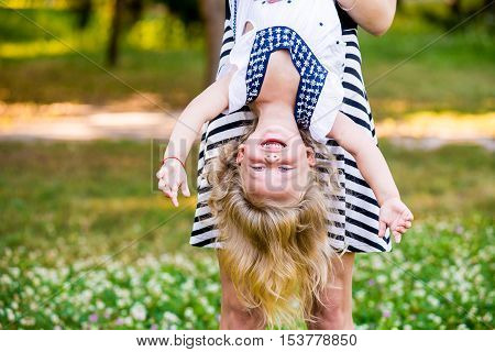 Young mom and cheerful adorable blond tot girl playing having fun together in park in summertime mother playfully holding her cute little daughter upside down close up