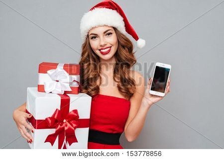 Smiling woman with gifts and phone. gifts in one hand and phone in other hand. Santa's helper. Dress and Santa's hat