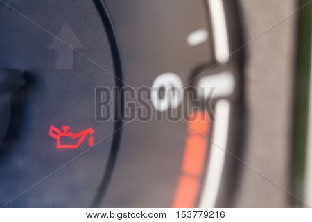 Detail of the dashboard of a car with the oil alert icon lit up.
