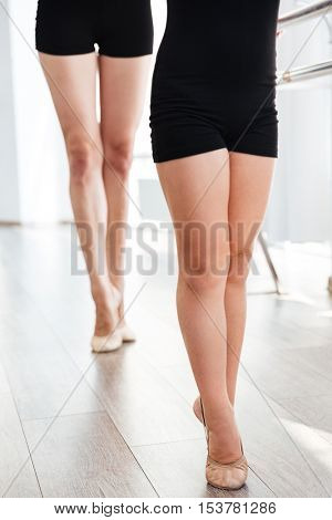 Closeup of legs of little beautiful ballerina and her teacher dancing tiptoes in ballet class