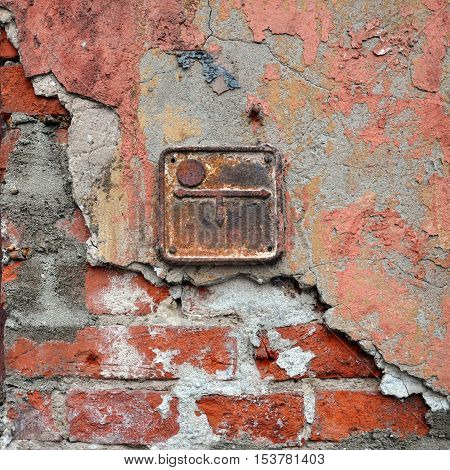 Vintage texture. Geodesic metal tag on the wall of cracked plaster and brick red.