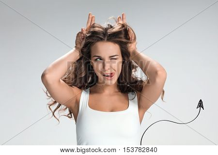 The young woman's portrait with funny happy emotions on gray background in image devil