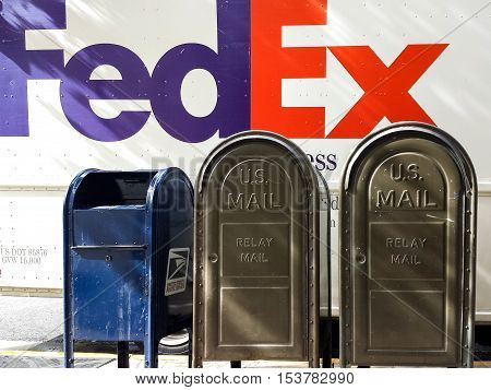 Hawaii, USA - Dec 18, 2015: FedEx and US mail postal boxes on the side of a road.