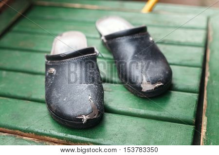 Old worn-out shoes with holes. Black boots poor needy person
