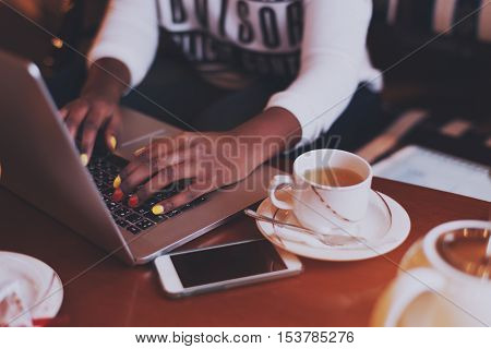 Hands of young black african american girl in a cafe at daytime wearing a long sleeve shirt. She is working on laptop and drinking tea, nail art, vintage color filter
