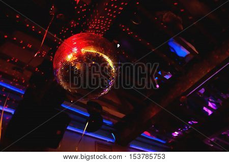 Shining bright red mirror disco ball. Interesting device for discotheque dancing party with music in night club.