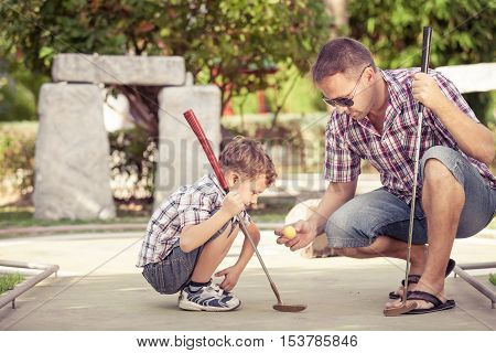 Sharing with golf experience. Cheerful young man teaching his son to play mini golf at the day time. Concept of friendly family.
