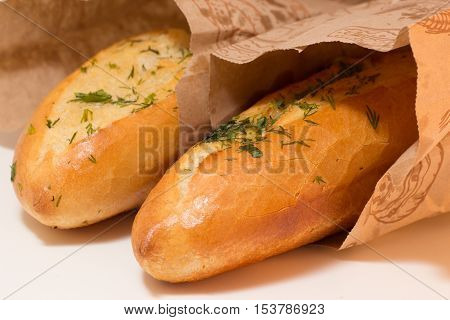 two baguettes covered with greens potherbs herbs in paper bags closeup shot
