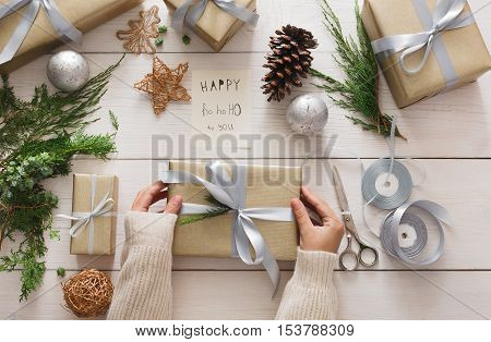 Winter holidays celebrating. Gift wrapping and decorating. Packaging modern christmas present boxes in paper with satin silver ribbon. Top view of hands on white wood table with fir tree branches.
