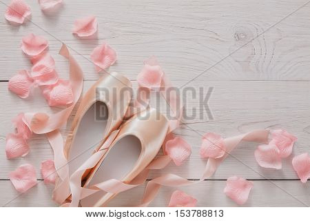 Pastel pink ballet shoes background. New pointe shoes with satin ribbon and rose petals lay on white rustic shubby chic wood, top view with copy space, soft toning
