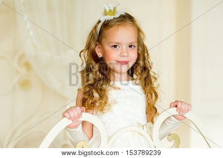 little princess on the bed in classic dress and vintage atmosphere of the room