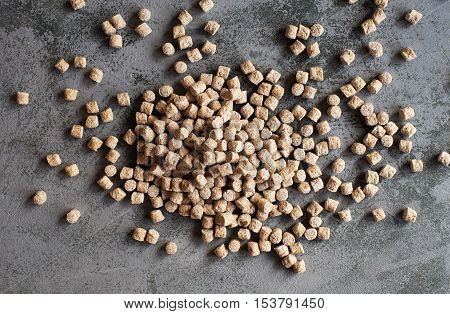 Pile of oat bran against grey background.Overhead view.