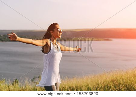 Successful sporty woman raising arms towards golden beautiful sunset and sea. Girl on cliff with copy space and lens flare