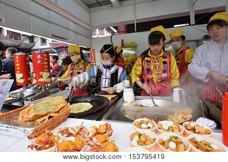 SHANGHAI CHINA - MARCH 19: Unidentified Chinese people trade traditional food in local market on March 19 2016 in Shanghai China. Shanghai is the largest Chinese city by population.
