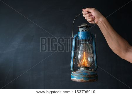 Old oil lamp on a background of black walls in the man's hand. The concept of lighting the way.