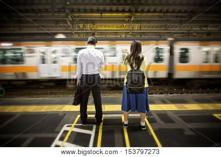 Unidentified businessman and schoolgirl wait for the daily commuter train. Tokyo, Japan.