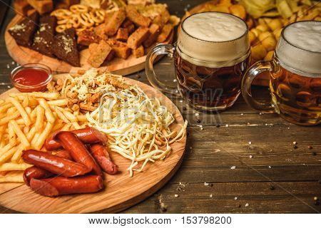 a variety of snacks for beer. Cheese, sausages, chips, snacks, potatoes, rustic, sauce the beer mugs on wooden background