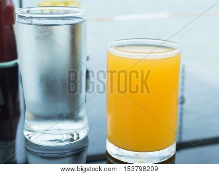Orange juice and cold water on table.