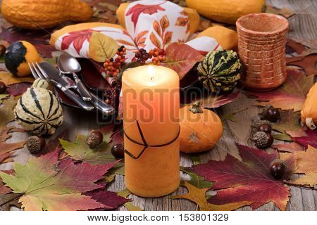 Selective focus of a close up view of holiday candle burning with autumn dinner setting with real gourd decorations leaves and acorns on top of rustic wood