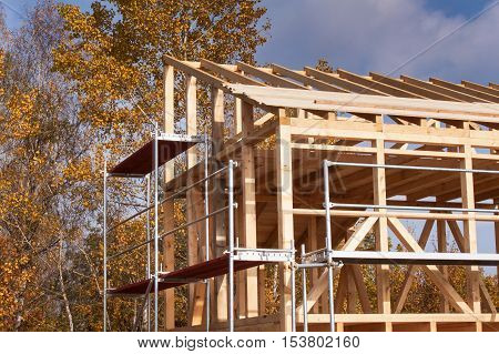 Metal scaffolding around the unfinished house. Construction of ecological house. Wooden frame of house under construction.Framed New Construction of a House. Timber house in building process poster