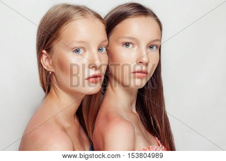 studio portrait of two young beautiful women. Beauty Woman face Portrait. Beautiful Spa model Girl with Perfect Fresh Clean Skin. Youth and Skin Care Concept.