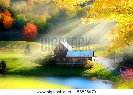 Morning sun light and rays over old barn near woodstock Vermont