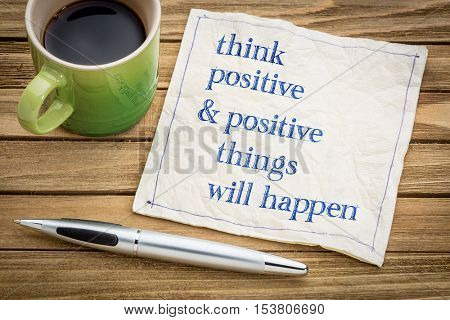 Think positive and positive things will happen - law of attraction concept - handwriting on a napkin with a cup of coffee