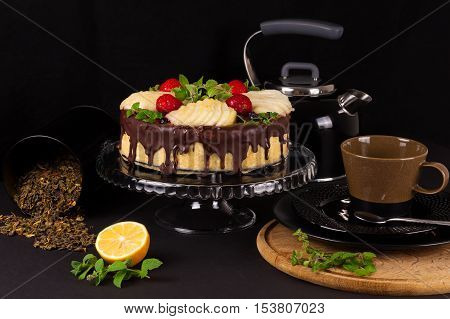 Cake with dark chocolate mousse, pear confit, fruits and berries on top as decoration. Tea party with homemade fresh cake.