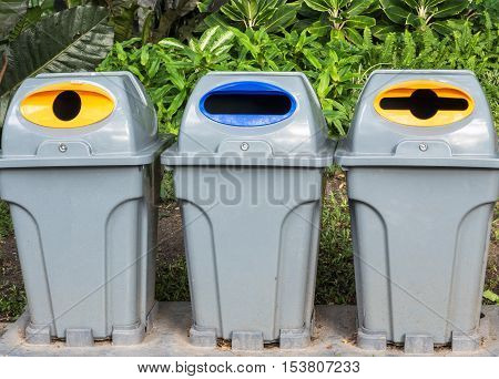 Three trashcan in park for separation of garbage.