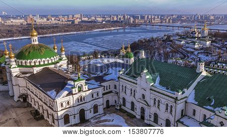 Panoramic view of Kiev Pechersk Lavra Monastery in winter. The Dnieper River, Refectory Church, Church of the Nativity of the Virgin Mary, bell towers of Near and Far Caves and the left bank of the city