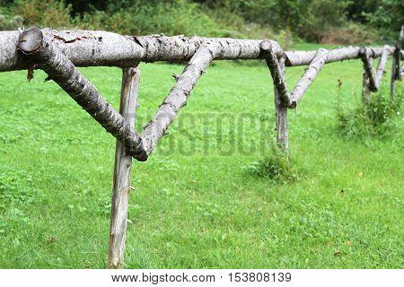Handmade wood fence made of tree trunks